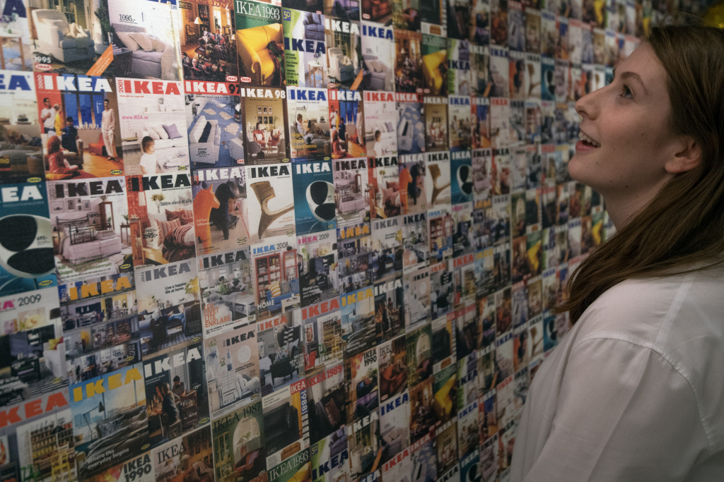 A member of staff poses next to a wall showing IKEA brochure covers over the last 30 years, in the IKEA house on October 17, 2017 in London, England.