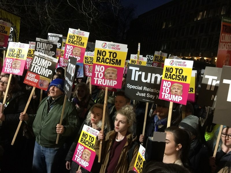 Protesters gathered outside the U.S. Embassy in London on Friday evening.