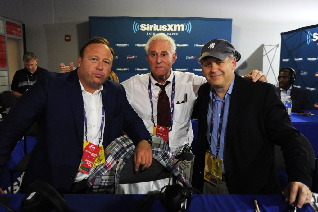 Alex Jones, of Infowars, Roger Stone, former Donald Trump advisor, and Jonathan Alter pose for a photo following an episode of Alter Family Politics on SiriusXM at Quicken Loans Arena on July 20, 2016 in Cleveland, Ohio.
