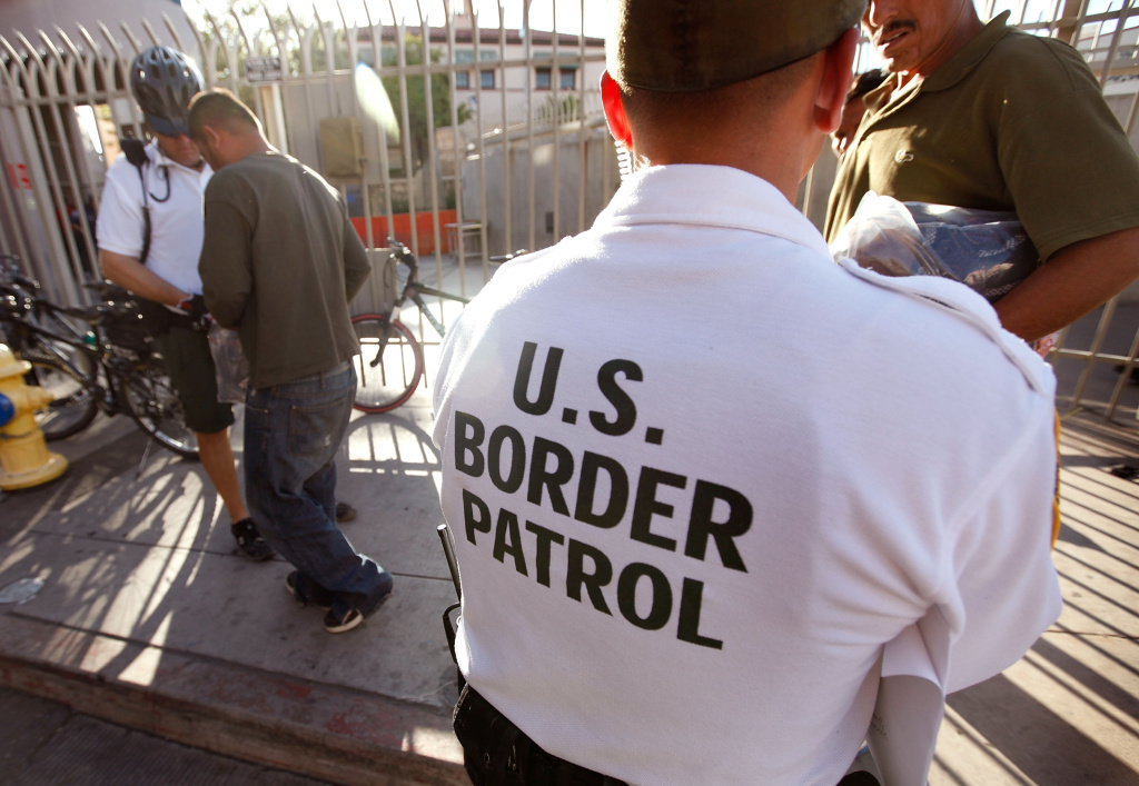 An U.S. Customs and Border Protection bike patrol agent assists Mexican's being returned to Mexico after they were apprehended for entering the United States illegally June 2, 2010 in Nogales, Arizona.