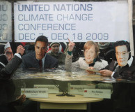 Activists dressed as (from L to R) leaders Abdoyale Wade of Senegal, Barack Obama of the USA, Angela Merkel of Germany and Hu Jintao of China pretend to debate in a giant aquarium filling with water on December 5, 2009 in Berlin, Germany.
