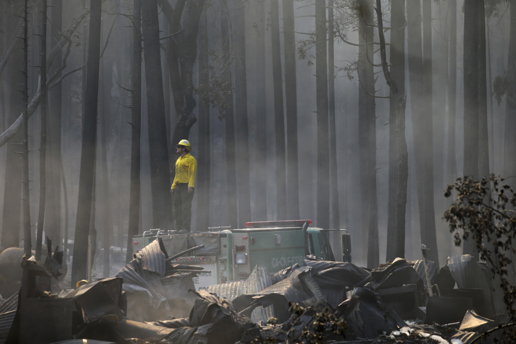 A firefighter stands on top of a fire truck at a campground destroyed by the Rim Fire near Yosemite National Park, Calif., on Monday, Aug. 26, 2013. Crews working to contain one of California's largest-ever wildfires gained some ground Monday against the flames threatening San Francisco's water supply, several towns near Yosemite National Park and historic giant sequoias. (AP Photo/Jae C. Hong)