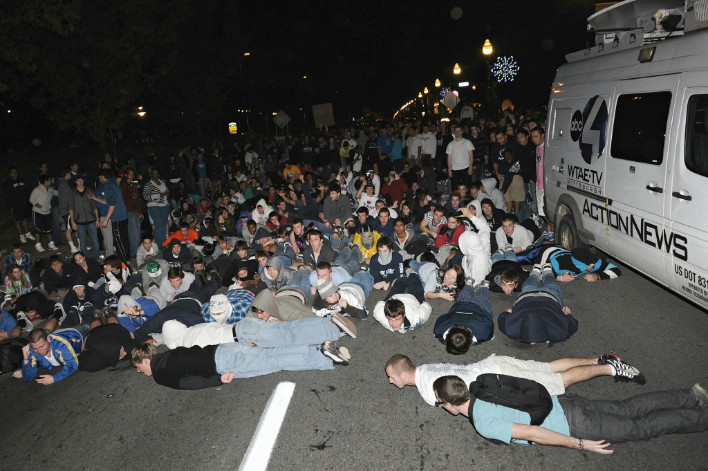 Police try to control students and those in the community as they fill the streets and after the firing of football head coach Joe Paterno, State College, PA, 2011.