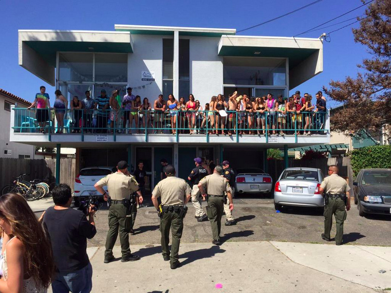 File: Santa Barbara County Sheriff's Office deputies approach a group of young people during the Deltopia spring break party in the Isla Vista neighborhood of Santa Barbara on Saturday, April 4, 2015.
