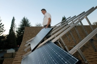 Phil Tussing installs photovoltaic solar panels on a residence in Portland, Oregon.