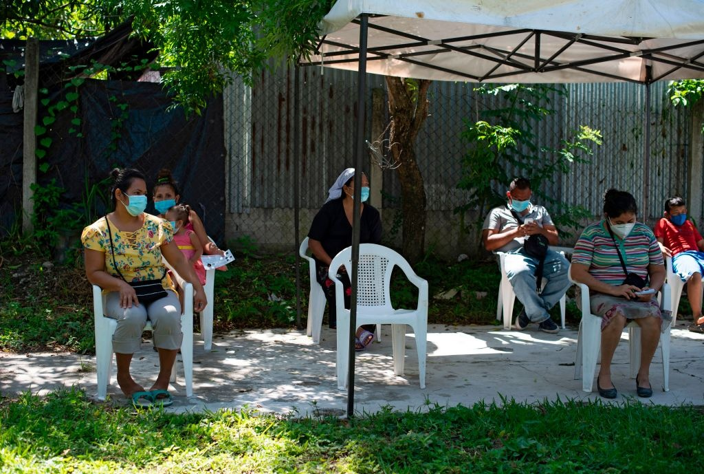 Residents maintain social distance while waiting to see a doctor in a clinic of the organization Doctors Without Borders (MSF) installed at the December 1 community in Soyapango, El Salvador, on July 30, 2020, amid the new coronavirus pandemic.