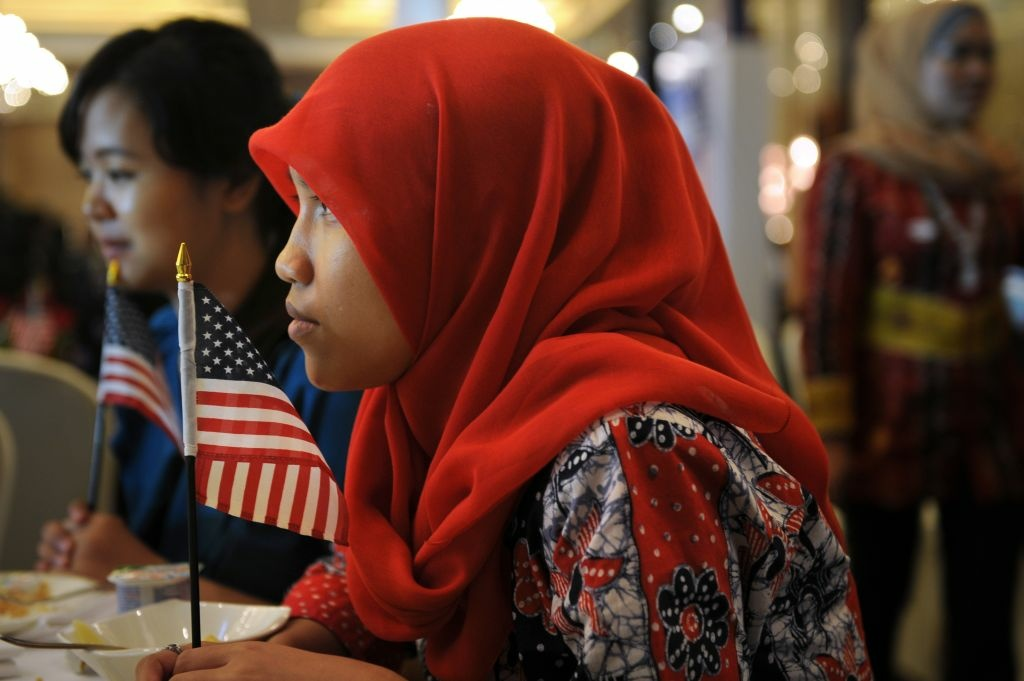 Indonesian student of international relations Anisa Widya Lestari, (C), 20, holds a US flag as visitors watch US presidential elections.