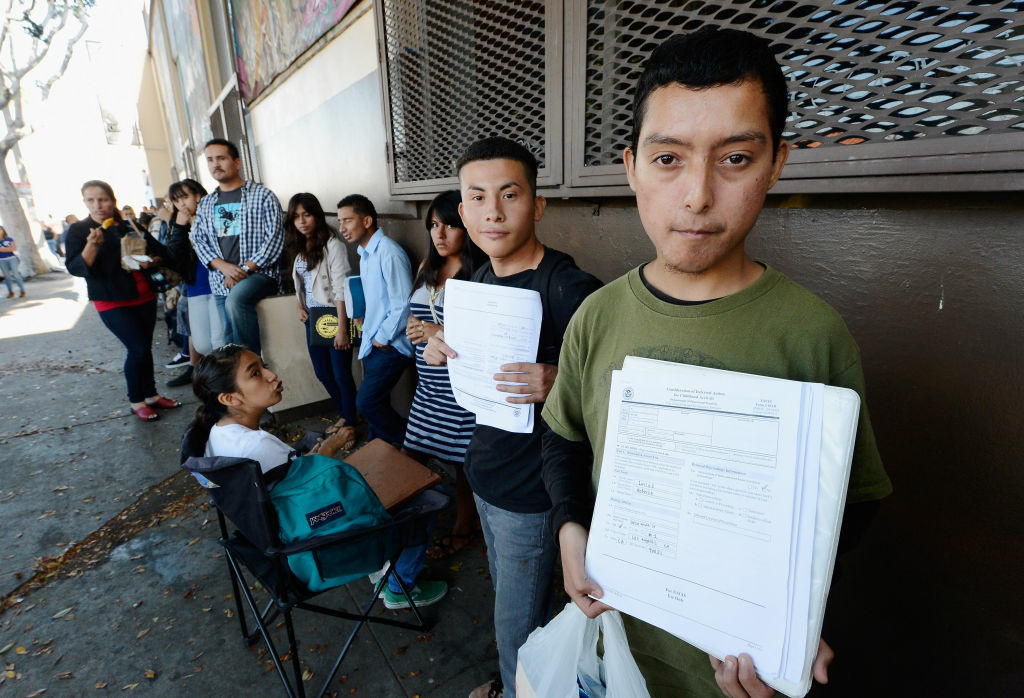 Roberto Larios, 21, right, holds a Deferred Action for Childhood Arrival application as he waits in line with hundreds of prospective applicants at the Coalition for Humane Immigrant Rights of Los Angeles office on August 15, 2012 .