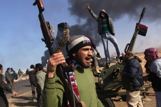 Libyan rebels gather on the frontline as smoke from a burning oil facility darkens the sky on March 11, 2011