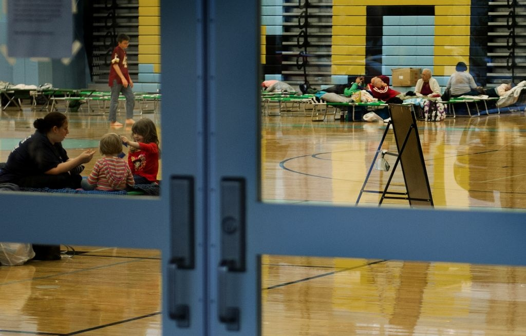 Families are seen through the door leading to the gymnasium of Cape Henlopen High School which is being used as a Red Cross shelter in Lewes, Delaware, October 28, 2012 as they await Hurricane Sandy's eminent landfall in the area.