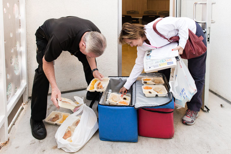 Volunteers Mike and Kathy Kearin sort through the hot and frozen meals before delivering them to 14 residents at an apartment building in Venice, Calif., in November 2016.