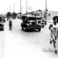 In the 4600 block of W. Washington Boulevard, a runner in a LAAC (Los Angeles Athletic Club) tank top participates in the qualifying round for the marathon to be held during the 1932 Olympic Games; motorists look on.