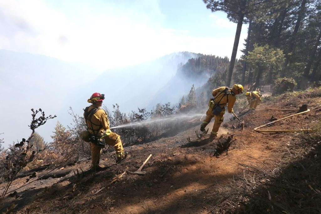 Firefighters hose down hot spots of the King Fire near Pollack Pines, Calif., Monday, Sept. 15, 2014. The fire, which started Sunday has consumed more than 3,000 acres and forced the evacuation of dozens of homes. (AP Photo/Rich Pedroncelli)