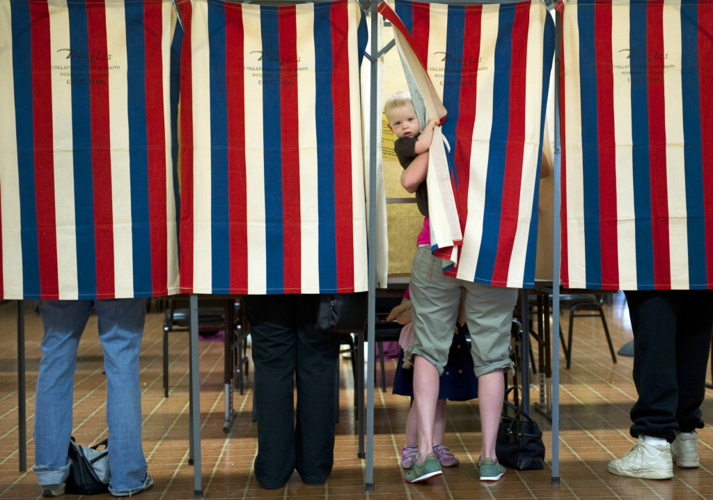 A child peeks out of the voting booth.