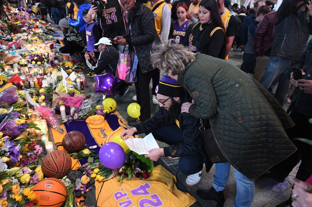 Fans gather at a makeshift memorial to mourn the death of NBA legend Kobe Bryant, who was killed along with his daughter and seven others in a helicopter crash on January 26, at LA Live plaza in front of Staples Center in Los Angeles on January 27, 2020.
