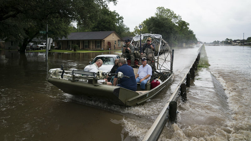 Residents and emergency workers in Houston are struggling to cope with intense flooding and rains brought by Hurricane Harvey. Volunteers use an air boat to rescue people from their flooded homes along Beamer Road in Houston, on Sunday.