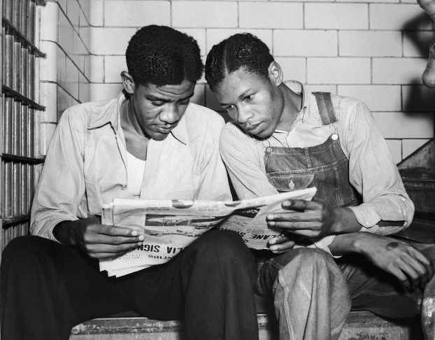 In this July 16, 1937 file photo, Charlie Weems, left, and Clarence Norris, Scottsboro case defendants, read a newspaper in their Decatur, Ala. jail after Norris was found guilty for a third time by a jury which specified the death penalty. Weems was to be tried a week later. Nine black teenagers known as the Scottsboro Boys were convicted by all-white juries of raping two white women on a train in Alabama in 1931. All but the youngest were sentenced to death, even though one of the women recanted her story. All eventually got out of prison, but only one received a pardon before he died.
