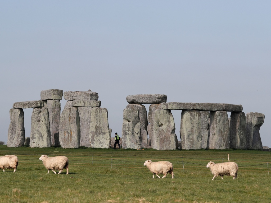 Sheep graze in front of southern England's Stonehenge in April. Scientists say they've determined some of the structure's sandstone megaliths came from 15 miles away.