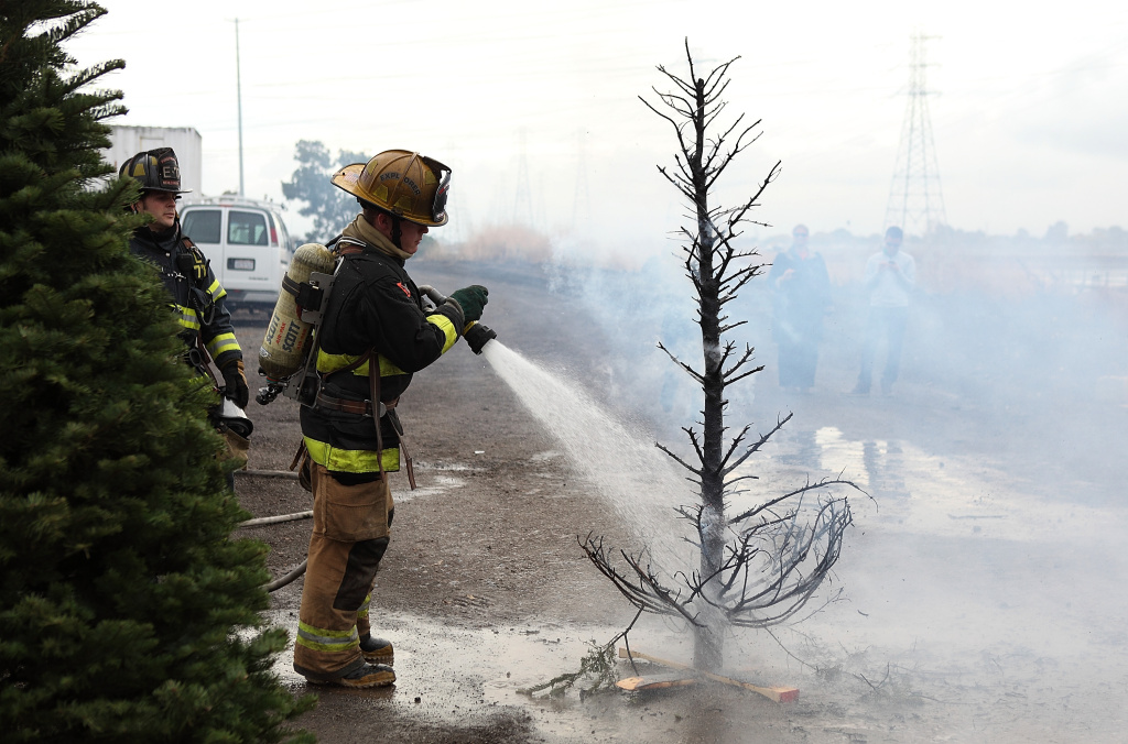 A Menlo Park fire department cadet extinguishes a Christmas tree fire during a holiday safety live fire demonstration on December 9, 2010 in Menlo Park, California. The Menlo Park fire department held their annual holiday safety live fire demonstration to promote fire safety during the holidays. Demonstrations using live fire showed how quickly fires can consume a home when a dry Christmas tree comes in contact with fire or candles are left unattended.
