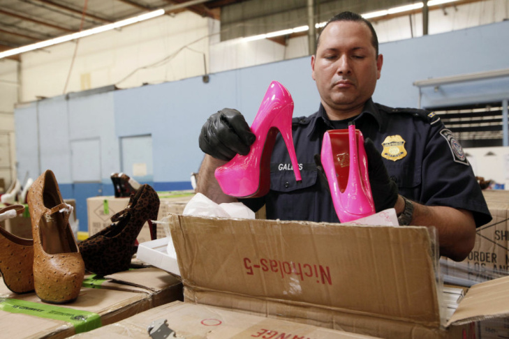 Pete Galles, U.S  Customs and Border Protection officer, opens a box containing some of the more than 20,000 pairs of counterfeit luxury shoes seized Aug. 14, 2012 in Long Beach from a shipment from China. U.S. Customs and Border Protection Spokesman Jaime Ruiz says four shipments of fake Christian Louboutin shoes were seized Tuesday, and another shipment was seized July 27.