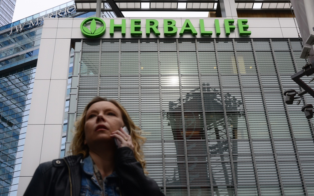 A woman is seen speaking on her cellphone beneath a Herbalife sign atop an office building in downtown Los Angeles on January 24, 2014. Herbalife said Wednesday it is being investigated by the Federal Trade Commission.