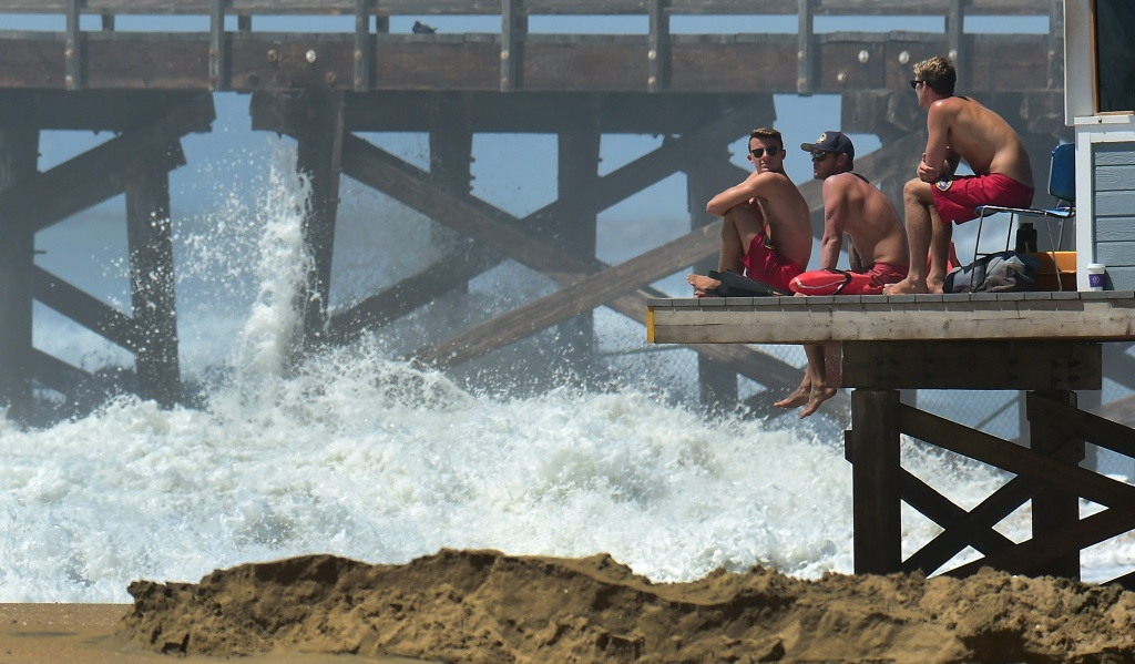 Lifeguards keep watch as big waves crash ashore near the pier at Seal Beach, California on August 27, 2014. Some coastal communities are already seeing the effects of sea level rise.