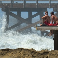 Lifeguards keep watch as big waves crash ashore near the pier at Seal Beach.