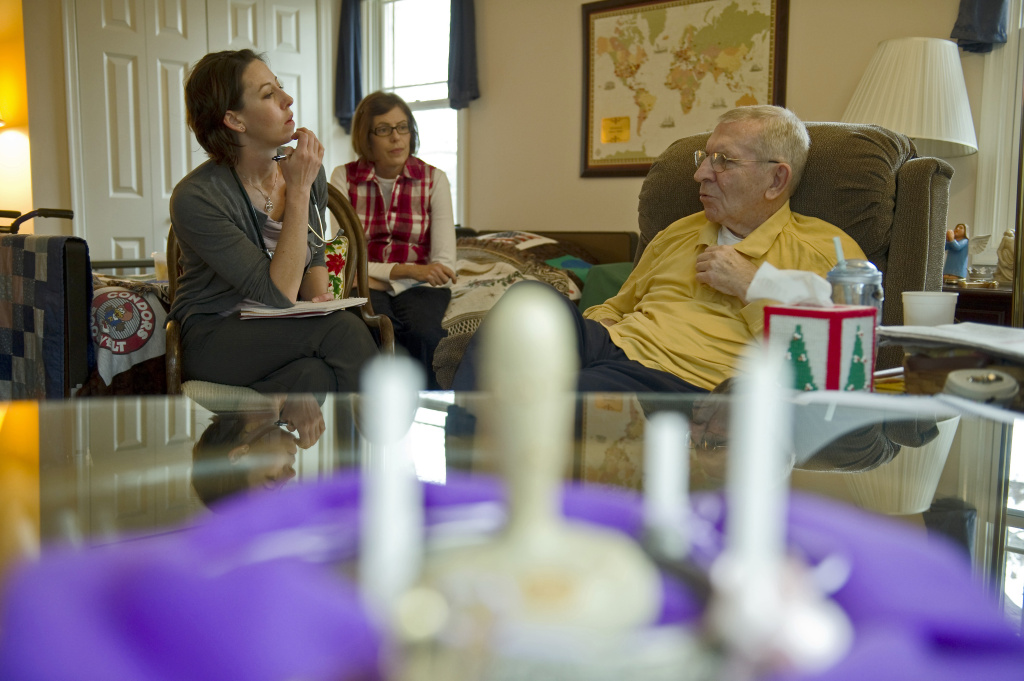 Neurologist Farrah Daly (L) speaks with 74-year-old patient Alton Hlavin (R), who is suffering from cortical basal degeneration, similar to Parkinson's disease, which gradually attacks nerve cells, causing debilitating muscle pain and shrinking parts of the brain until the patient can no longer walk or talk, as his wife Martha (C) looks on during a visit at their home in Vienna, Virginia, on December 10, 2010.