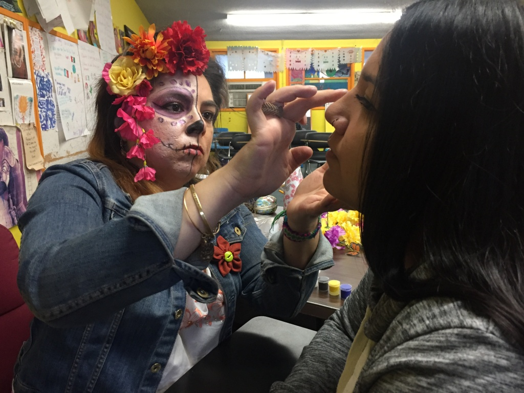Art and english teacher Learsi Martinez paints a red flower on the face of 17-year-old Jocelyn Cordova. Cordova, who lost her sister, says her sister loved red and flowers.