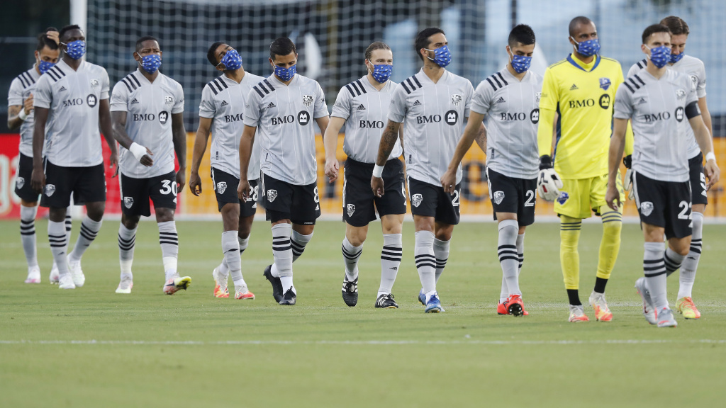 Members of the Montreal Impact, wearing masks, take the field for their match against Toronto FC as part of the MLS Is Back Tournament Thursday in Reunion, Fla.