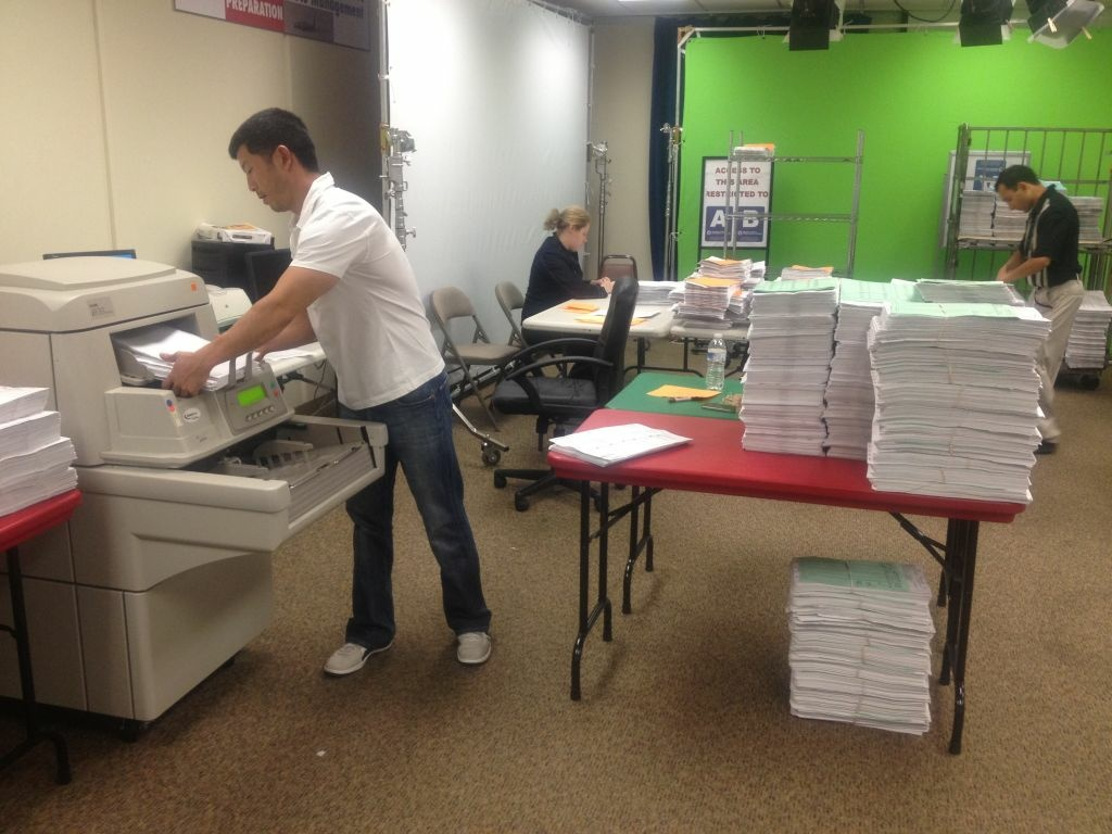 Workers process mail-in ballots at the Orange County Registrar's Office. Nearly half of Orange County's registered voters send their ballots in by mail, but so far the Registar has only seen 115,000 of 680,000 ballots.