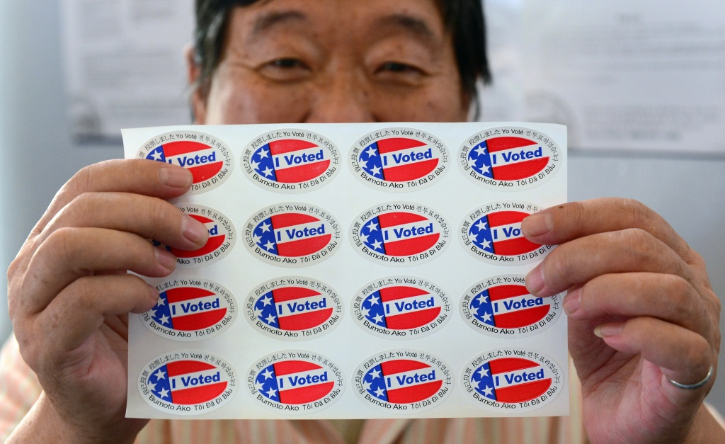 Election official Henry Tung displays a sheet of 'I Voted' stickers in various languages at a polling station at St. Paul's Lutheran Church in Monterey Park, Los Angeles, on November 6, 2012.