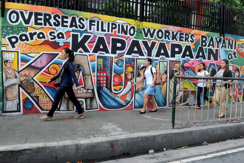 People walk past a mural honoring overseas Filipino workers in Manila on July 7, 2014. The government estimates there are ten million overseas Filipino workers, or about a 10th of the population, whose dollar remittances account for about 10 percent of gross domestic product.