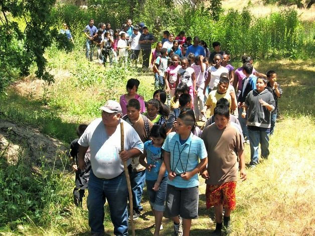Ron Goode, North Fork Mono Tribal Chairman, teaching children about California Indians and the land near one of the Tribe's restoration sites at Lost Lake in 2010.