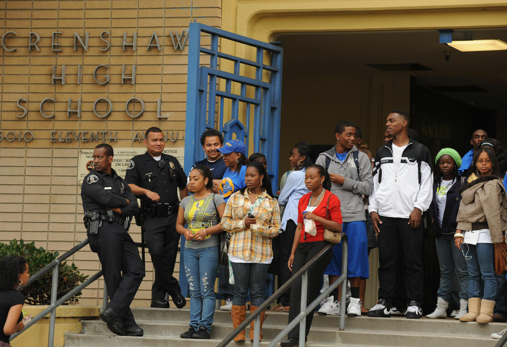 Students and police watch teachers, parents and students chanting slogans on a picket line outside Crenshaw High School to protest teacher layoffs planned by the Los Angeles Unified School District (LAUSD) in Los Angeles on May 15, 2009.