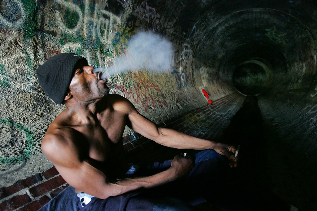 Donald Rayfield, known on the street as 'Detroit', smokes crack cocaine in an underground storm drain on January 18, 2006 in Los Angeles, California.