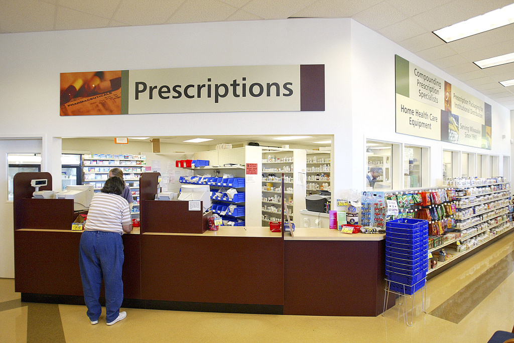 A customer picks up a prescription at Hi-School Pharmacy store in Milwaukie, Oregon.