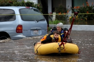 Jennifer Bowerman and her 7-year-old son Sabastian Bowerman are led across flood waters on a raft after being stranded in a hotel after a powerful rainstorm Dec. 22, 2010 in San Diego. Forty-seven guests were stranded at the Premiere Hotel after floodwaters rose and blocked them from getting to dry land.