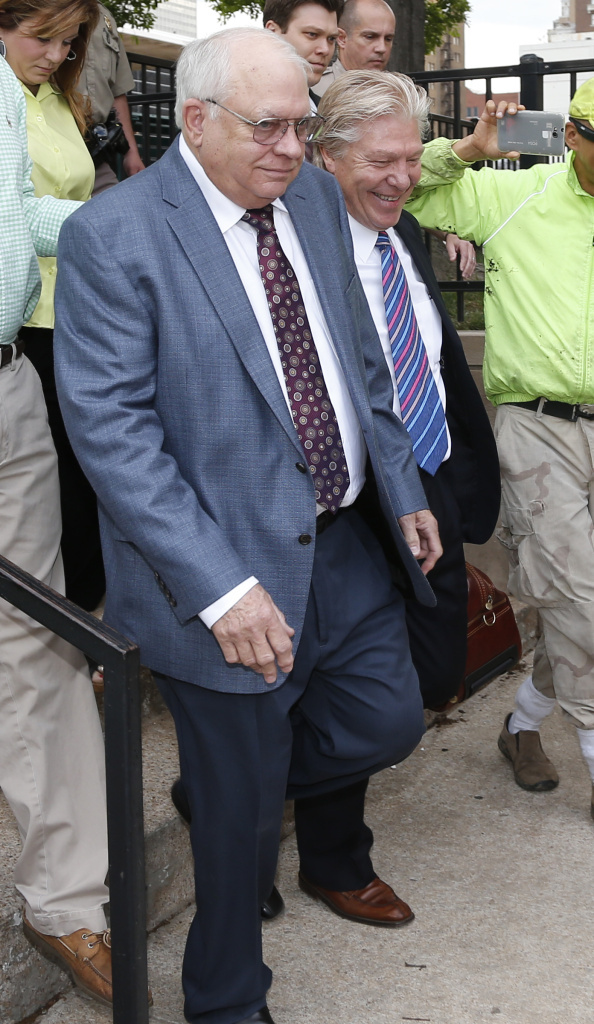 Tulsa County, Okla., reserve deputy Robert Bates leaves his arraignment with attorney Tuesday. Bates fatally shot a suspect who was pinned down by officers, raising alarms about volunteer police officers who wear badges and carry gun.