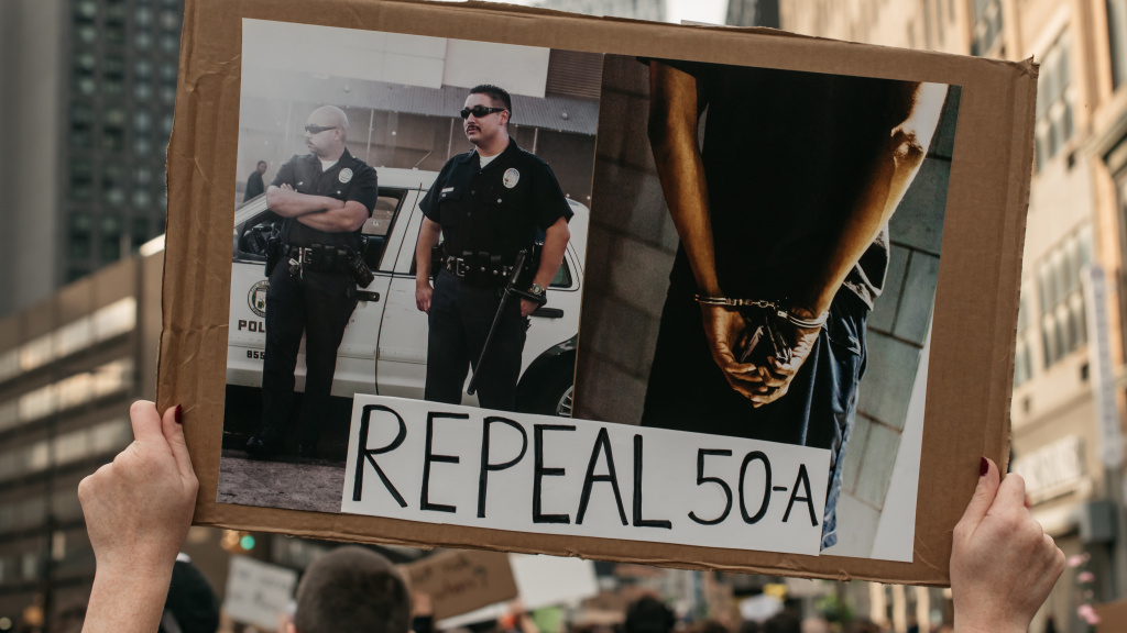 A protest sign calling for the repeal of 50-A, photographed during a march in Brooklyn denouncing police brutality and systemic racism.