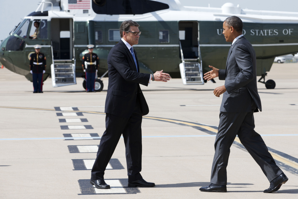 President Barack Obama, right, and Texas Gov. Rick Perry shake hands as Obama arrives in Dallas to attend a meeting on immigration on July 9, 2014.