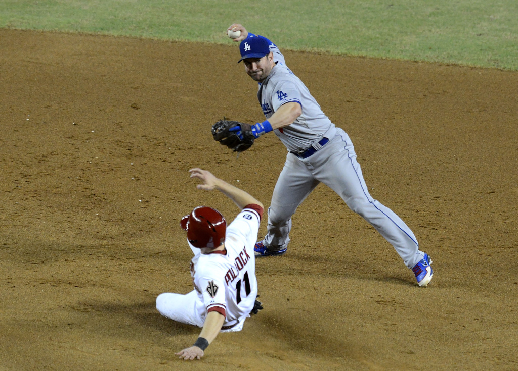 Nick Punto #7 of the Los Angeles Dodgers attempts to turn a double play as AJ Pollock #11 of the Arizona Diamondbacks slides into second base at Chase Field on September 17, 2013 in Phoenix, Arizona.