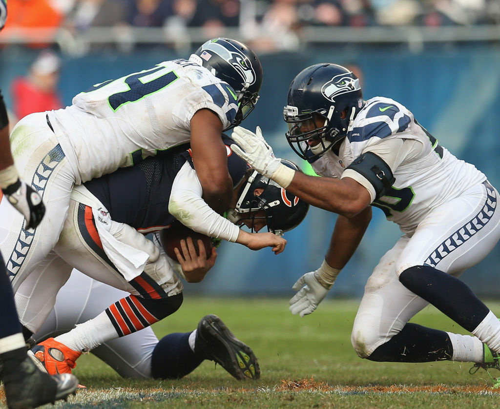 Jay Cutler #6 of the Chicago Bears is tackled by Bobby Wagner #54 and K.J. Wright #50 of the Seattle Seahawks at Soldier Field on December 2, 2012 in Chicago, Illinois. The Seahawks defeated the Bears 23-17 in overtime.