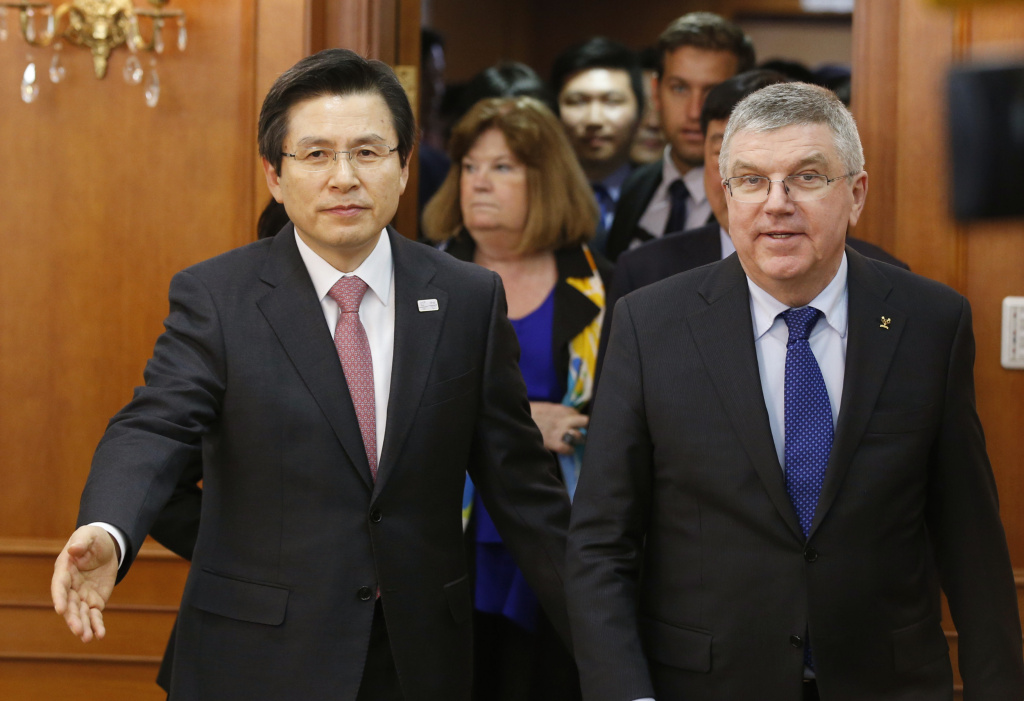 International Olympic Committee (IOC) President Thomas Bach, left, is escorted by South Korea's Prime Minister and acting President Hwang Kyo-ahn for a meeting in Seoul, South Korea, in this Tuesday, March 14, 2017 file photo. Bach has repeatedly hinted at awarding the hosting rights for both the 2024 and 2028 Games at the IOC Session on Sept. 13 in Lima, Peru — an unprecedented double vote.