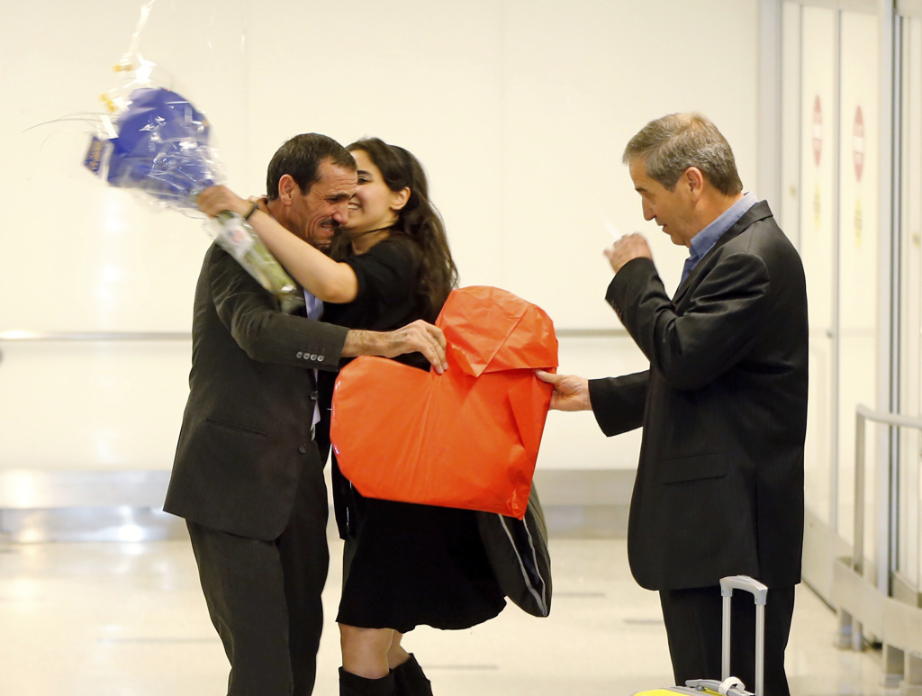 Ali Vayeghan, an Iranian citizen with a valid U.S. visa, left, is kissed by his niece Marjan Vayghan as his brother Houssein Vayghan welcomes him at Los Angeles International Airport on Feb. 2, 2017. Vayeghan had been turned away from LAX by President Trump's travel ban until a judge's ruling put the ban on hold.