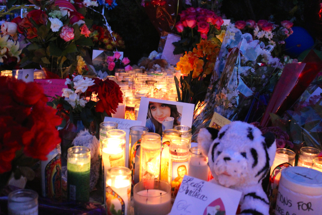 A picture of Andrea Gonzalez, one of three teens killed in a Halloween hit-and-run crash, is surrounded by candles at a roadside memorial in Santa Ana.