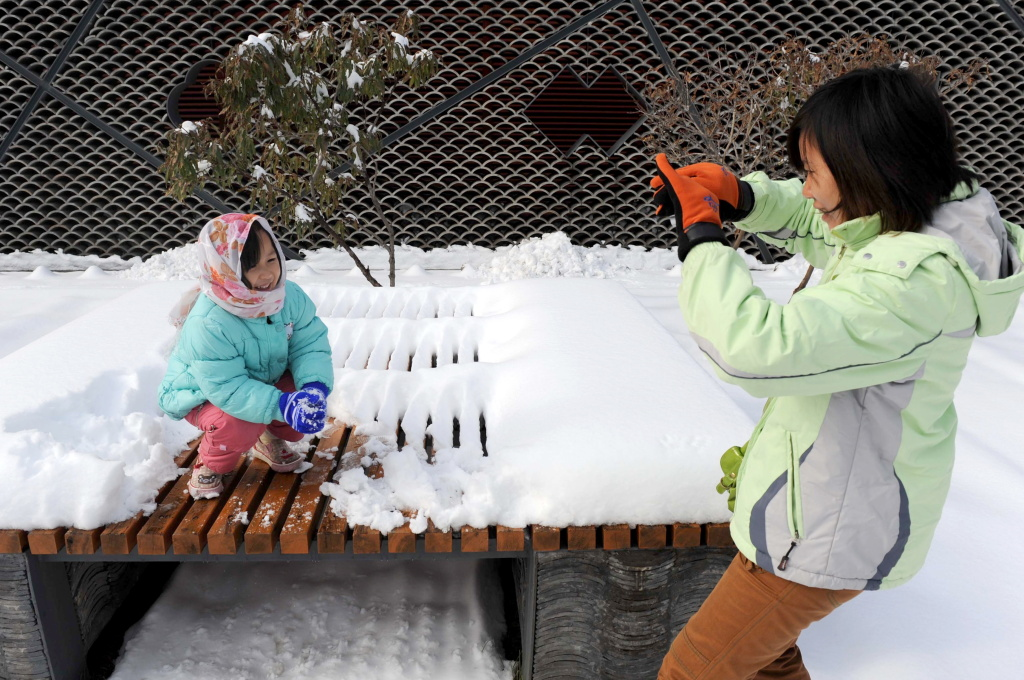 A woman takes photos of her daughter after a snowfall in Beijing on November 10, 2009.