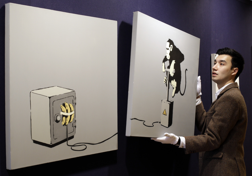 An auction house employee poses for the photographers holding part of a 2002 stencil spray paint and emulsion on canvas diptych art piece by Banksy, at an exhibition in central London, Friday, April 12, 2013. For the first time in the United States, an original Banksy street mural is going up for auction in December.