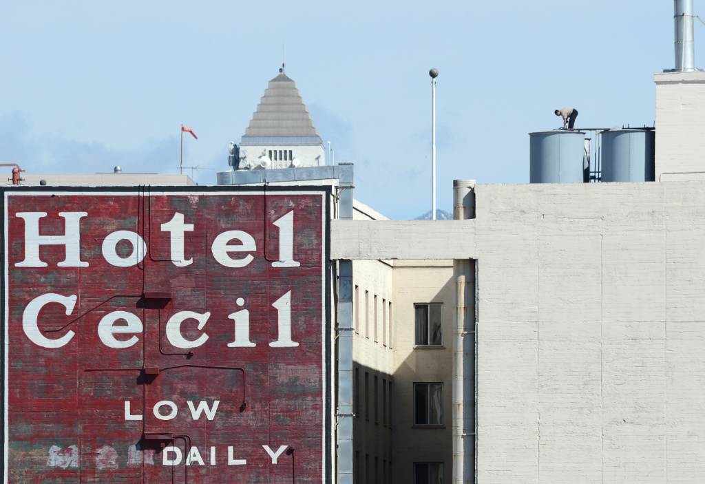 A worker stands on a water tank on the roof of the Hotel Cecil in Los Angeles, California on February 20, 2013. The body of 21-year-old Canadian tourist Elisa Lam was found in a water tank on the roof of the hotel three weeks after she went missing.