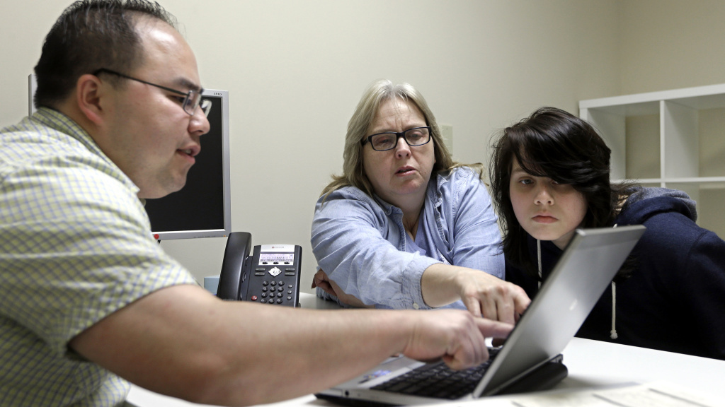 Enrollment counselor Vue Yang (left) reviews health insurance options for Laura San Nicolas (center), accompanied by her daughter, Geena, 17, at Sacramento Covered in Sacramento, Calif., in February.